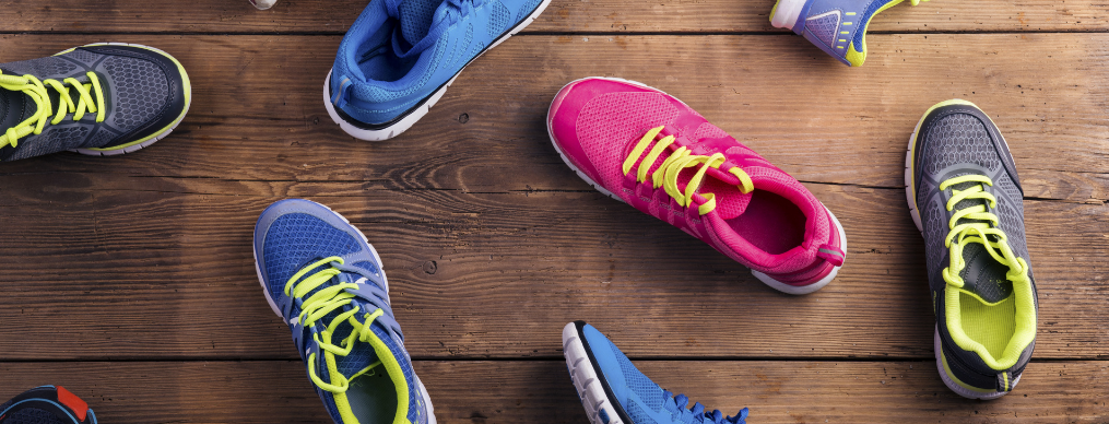 variety of running shoes on wooden floor background